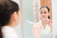 Portrait of young beautiful woman brushing her teeth with toothbrush. royalty free stock photos