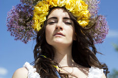 Portrait of young beautiful woman with circlet of flowers on her hair. Portrait of young beautiful woman circlet of flowers on head outdoors Royalty Free Stock Photography