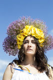 Portrait of young beautiful woman with circlet of flowers on her hair. Portrait of young beautiful woman circlet of flowers on head outdoors Royalty Free Stock Images
