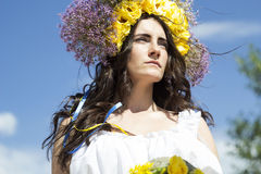 Portrait of young beautiful woman with circlet of flowers on her. Portrait of young beautiful woman circlet of flowers on head outdoors Stock Photography