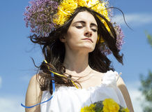 Portrait of young beautiful woman with circlet of flowers on her. Portrait of young beautiful woman circlet of flowers on head outdoors Royalty Free Stock Images