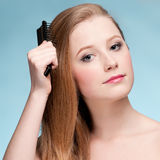 Portrait of young beautiful woman with comb Stock Photography