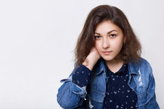 A portrait of young beautiful woman with dark hair and eyes wearing jean jacket with black shirt holding her hand on her neck look. Ing confident into camera Stock Photography