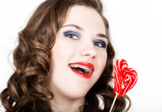 Portrait of young beautiful woman with dental braces holding sugarplum Royalty Free Stock Images