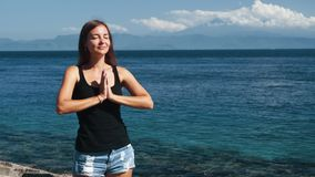 Portrait of young beautiful woman does yoga exercise, ocean on background. Girl meditates with closed eyes in summer day stock video