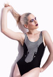 Portrait of young beautiful woman dressed in striped swimsuit po Stock Photo