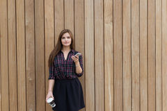 Portrait of a young beautiful woman dressed in stylish clothes holding mobile phone and take away coffee, Royalty Free Stock Photography
