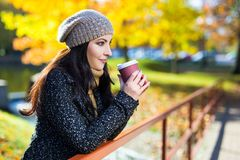 Portrait of young beautiful woman drinking coffee in autumn park Royalty Free Stock Photography