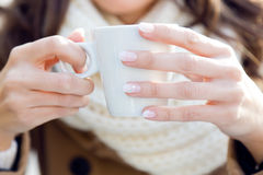 Portrait of young beautiful woman drinking coffee outdoor. Royalty Free Stock Photo
