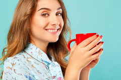 Portrait of young beautiful woman drinking coffee or tea over bl Royalty Free Stock Images