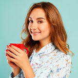 Portrait of young beautiful woman drinking coffee or tea over bl Stock Photo