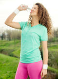 Portrait of young beautiful woman  drinking water at summer gree Royalty Free Stock Photography