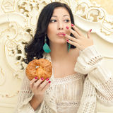 Portrait of young beautiful woman eating her croissant Stock Images