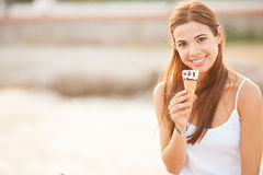 Portrait of a young beautiful woman eating ice-cream cone Stock Photography