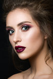 Portrait of young beautiful woman with evening make up. Over black background. Multicolored smokey eyes and dark red velvet mat lips. Luxury skincare and modern stock photography