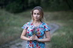 Portrait of young beautiful woman in flower dress holding flowers in her hands Stock Image