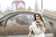 Portrait of a young and beautiful woman in a fur coat with cap a Royalty Free Stock Images