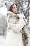 Portrait of a young and beautiful woman in a fur coat with cap a Royalty Free Stock Image