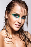 Portrait of young beautiful woman with green wet shining makeup Royalty Free Stock Photo