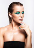 Portrait of young beautiful woman with green wet shining makeup Stock Photo