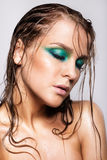 Portrait of young beautiful woman with green wet shining makeup Royalty Free Stock Photos