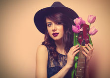 Portrait of a young beautiful woman with guitar and tulips Royalty Free Stock Image