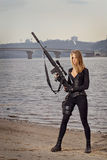 Portrait of young beautiful woman with a gun. Portrait of young beautiful woman holding M16 rifle at dramatic background Royalty Free Stock Images