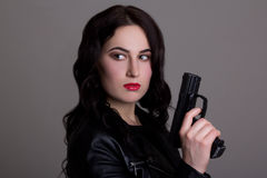 Portrait of young beautiful woman with gun over grey Royalty Free Stock Photos