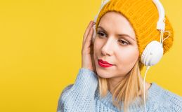Portrait of a young beautiful woman with headphones in studio on a yellow background. Stock Photo
