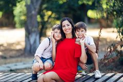 Portrait of a young beautiful woman with her son and nephew. Portrait of a young beautiful women with her son and nephew. They are sitting on the bench royalty free stock photo