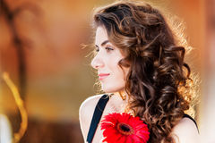 Portrait of young beautiful woman holding a red flower Royalty Free Stock Image