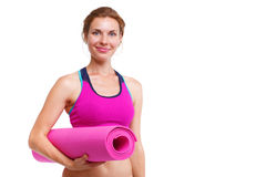 Portrait of young beautiful woman holding yoga mat - isolated. royalty free stock photography