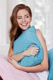 Portrait of a young beautiful woman hugging a pillow Royalty Free Stock Image