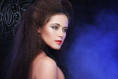 Portrait of young beautiful woman with long brown  hair and red. Lipstick over dark background Royalty Free Stock Photos