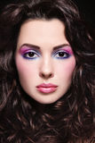 Curly hair. Portrait of young beautiful woman with long curly hair and fancy make-up royalty free stock image