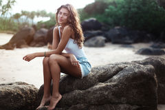 Portrait of a young beautiful woman with long curly hair at the seaside Stock Image