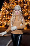 Portrait of young beautiful woman with long fair hair outdoor in a cold winter day. Beautiful blonde girl in winter clothes. With xmas lights in background Royalty Free Stock Images