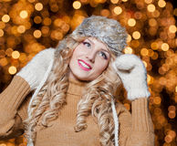 Portrait of young beautiful woman with long fair hair outdoor in a cold winter day. Beautiful blonde girl in winter clothes. With xmas lights in background Stock Images
