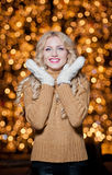 Portrait of young beautiful woman with long fair hair outdoor in a cold winter day. Beautiful blonde girl in winter clothes. With xmas lights in background Stock Photos