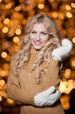 Portrait of young beautiful woman with long fair hair outdoor in a cold winter day. Beautiful blonde girl in winter clothes. With xmas lights in background Royalty Free Stock Image