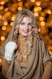 Portrait of young beautiful woman with long fair hair outdoor in a cold winter day. Beautiful blonde girl in winter clothes. With xmas lights in background Stock Image