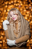 Portrait of young beautiful woman with long fair hair outdoor in a cold winter day. Beautiful blonde girl in winter clothes. With xmas lights in background Royalty Free Stock Photography