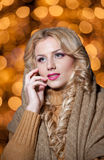 Portrait of young beautiful woman with long fair hair outdoor in a cold winter day. Beautiful blonde girl in winter clothes. With xmas lights in background Royalty Free Stock Photos