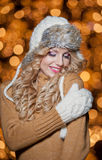 Portrait of young beautiful woman with long fair hair outdoor in a cold winter day. Beautiful blonde girl in winter clothes. With xmas lights in background Royalty Free Stock Photo