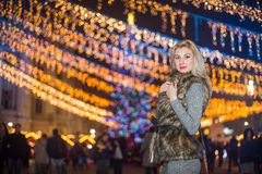 Portrait of young beautiful woman with long fair hair outdoor in cold winter evening. Beautiful blonde girl in winter clothes Royalty Free Stock Photo
