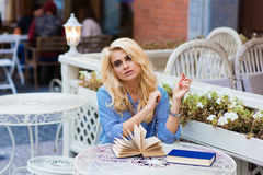 Portrait of a young beautiful woman with luxury blonde hair sitting with books in sidewalk cafe in warm spring day, Stock Photo