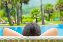 Portrait of a young beautiful woman lying on against the pool on Royalty Free Stock Photo