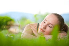 Portrait of young beautiful woman lying in grass Stock Photography