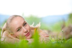 Portrait of young beautiful woman lying in grass Royalty Free Stock Images