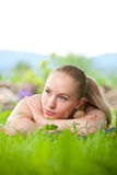 Portrait of young beautiful woman lying in grass Stock Image